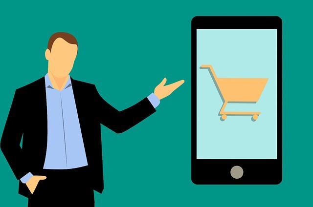 muž v saku ukazující na displej telefonu s nákupním košíkem.jpg